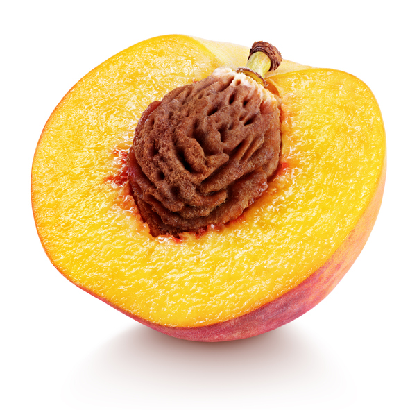 half of peach fruit with nut isolated on white